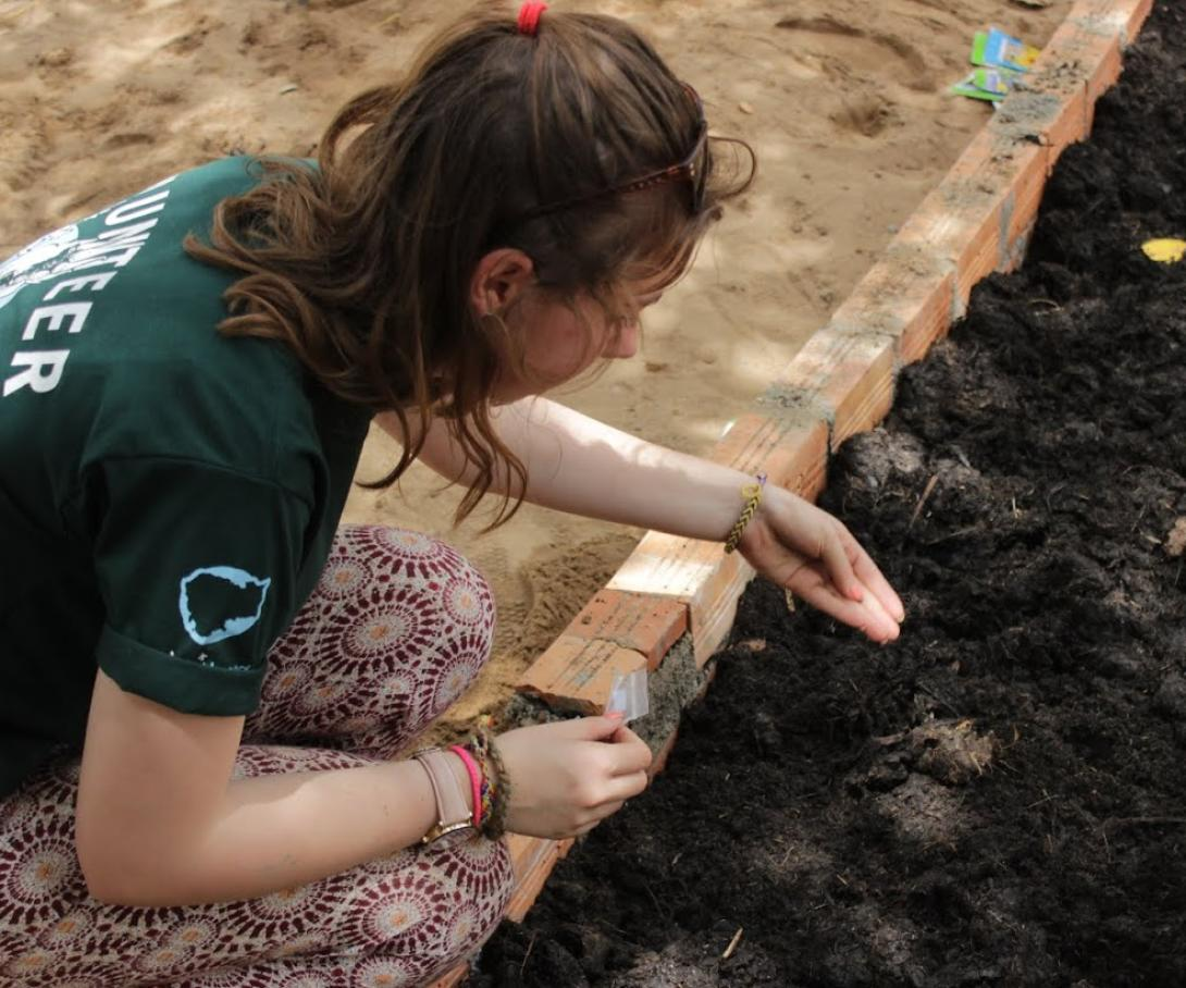 An Anglia Girl Guide plants seeds at a school during her group volunteer trip to Cambodia.